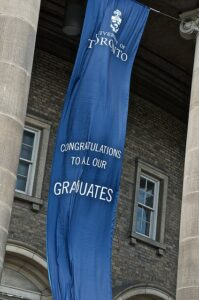 A University of Toronto blue, vertical banner fixed to cables outside of the Convocation Hall building. It reads congratulations to all our graduates.