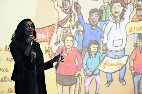 Professor Rupaleem Bhuyan standing in front of an illustration projected on to a screen, she is speaking into a microphone.